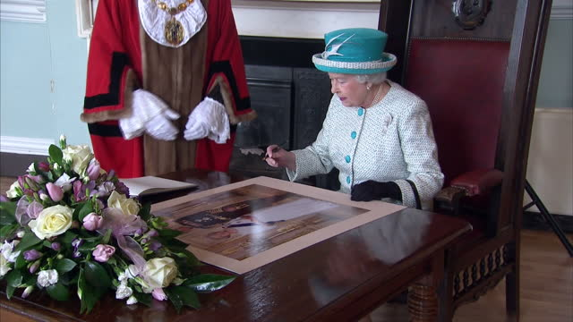 interior shots queen elizabeth ii signing photograph and book in king's lynn town hallthe queen has renewed her pledge of service to the nation sixty... - the queen stock videos and b-roll footage