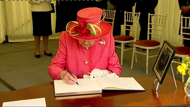 Interior shots Queen Elizabeth II talking with official and signs guest book whilst on visit to Salvesen Gardens a new housing development for...