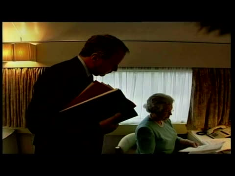 interior shots queen elizabeth ii working at desk on royal train speaking to aide exterior shot royal train in siding in countryside interior close... - elizabeth ii stock videos & royalty-free footage
