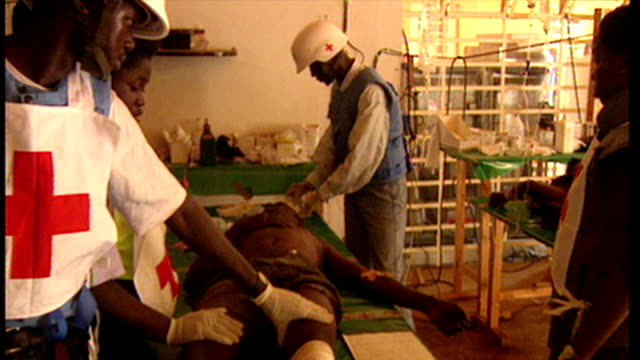 interior shots red cross medical volunteers treating man injured in fighting during the rwandan civil war on june 16 1994 in various cities rwanda - völkermord stock-videos und b-roll-filmmaterial