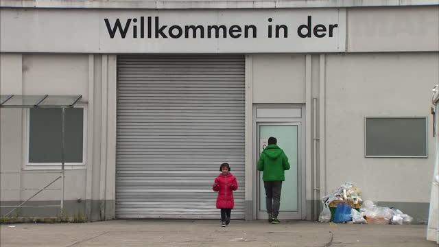 Interior shots refugees at relief centre in Munich Exterior shots entrance makeshift migrant relief shelter signage 'WILLKOMMEN IN DER' on September...