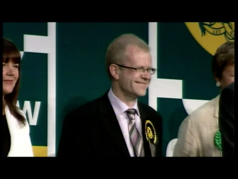 Interior shots returning officer reading out vote results SNP candidate John Mason celebrating victory Interior shots John Mason MP delivering...