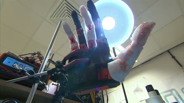 Interior shots Roboticist lab worker sat at desk working on robotic hand robotic hand moves its digits in test whilst being held in vice on September...