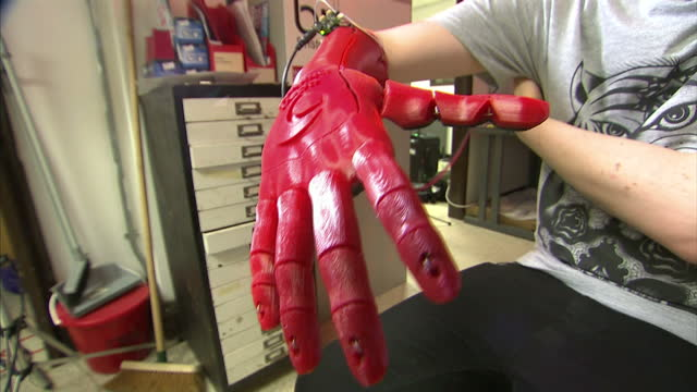 Interior shots Roboticist lab worker showing off red 3D printed robotic arm at Open Bionics Lab on September 04 2015 in Bristol England