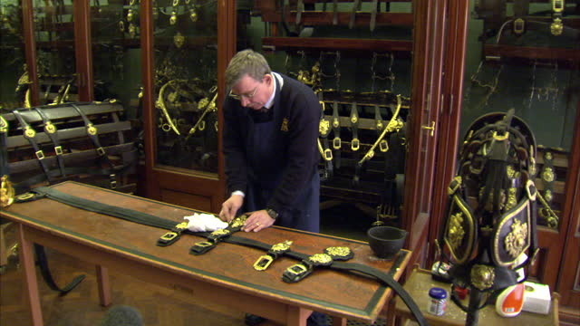 interior shots royal mews member of staff cleaning brass insignia on state royal horse wear preparations for the royal wedding at the mews on march... - brass stock videos & royalty-free footage