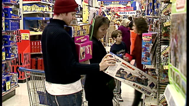 interior shots shoppers browsing toys on shelves in toys r us store and selecting items to purchase. on december 13, 1996 in london, england. - negozio di giocattoli video stock e b–roll