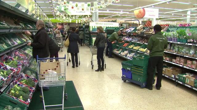 interior shots shoppers walking around fruit vegetable aisle of supermarket staff stacking shelves in supermarket shoppers in supermarket on october... - 生鮮食品コーナー点の映像素材/bロール