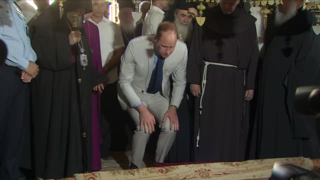 Interior shots show Prince William visiting The Church of the Holy Sepulchre watched the press photographers as he kneels down and Exterior shots...