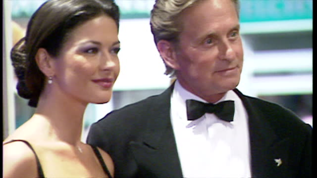 interior shots showing actress catherine zeta-jones and husband michael douglas arriving on red carpet for premiere of film entrapment. couple pose... - film premiere stock videos & royalty-free footage