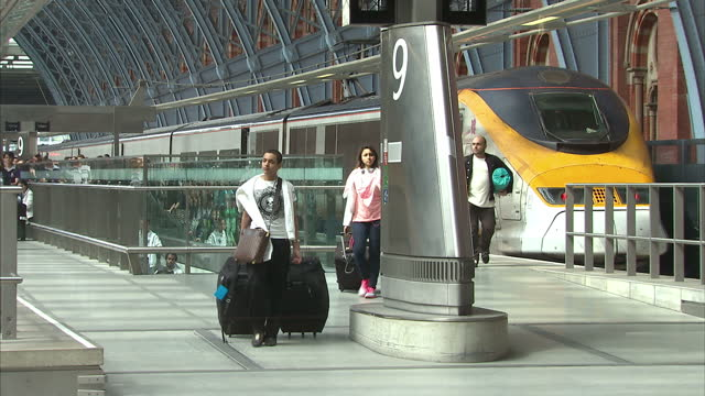 Interior shots St Pancras station terminus with passengers walking from Eurostar train at platform Interior shots passengers boarding Eurostar train...