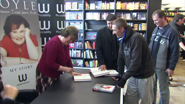 interior shots susan boyle signing copies of her autobiography for fans at book singing event susan boyle at book signing event on october 16, 2010... - スーザン ボイル点の映像素材/bロール