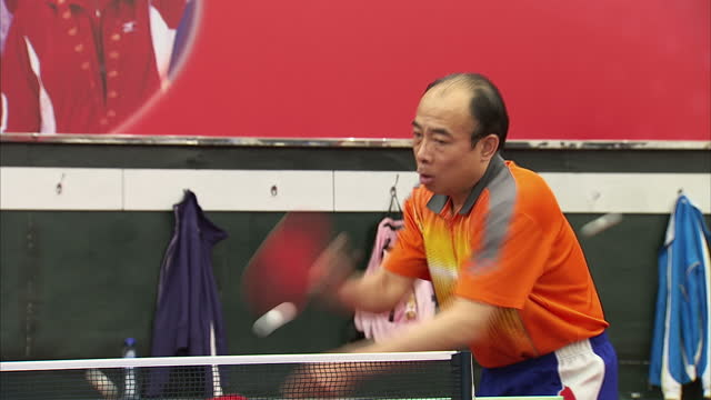 interior shots table tennis coach giving lesson, poster of chinese national team in background - national team stock videos & royalty-free footage