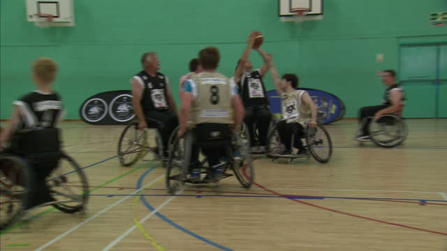 Interior shots team of disabled athletes in wheelchairs playing wheelchair basketball on court Athletes Play Wheelchair Basketball on August 22 2012...