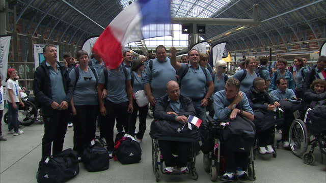 Interior shots the French Paralympic team arrive at St Pancras Station pose for photo call waving the Tricolour flag singing the national anthem...