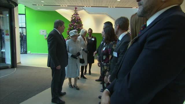 vídeos de stock, filmes e b-roll de interior shots the queen & camilla walk through lobby of barnados hq & shake hands workers to applause. the queen and camilla meeting barnados... - ilford