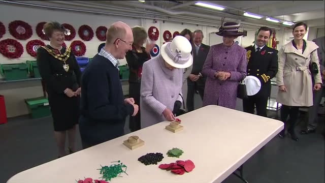 interior shots the queen helps finish off making a poppy on table interior shots the queen sits to sign a portrait of herself the visitors book the... - richmond upon thames stock-videos und b-roll-filmmaterial