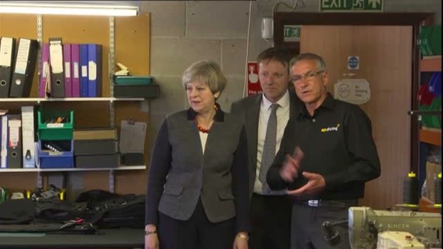 interior shots theresa may visits ap diving walks into office meets and chats with various workers sat at desks and work stations in helston on... - cornovaglia video stock e b–roll