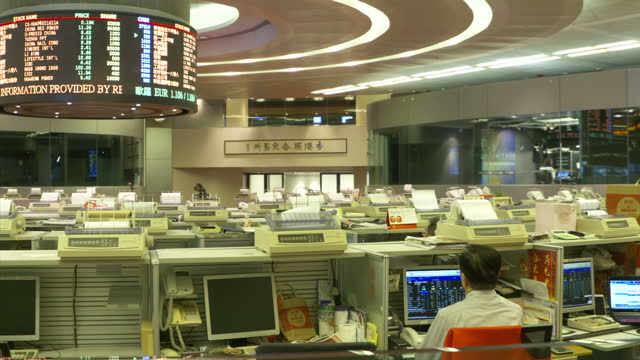 Interior shots traders working on HangSeng market trading floor with large screens showing stock names and prices on June 27 2016 in Hong Kong China