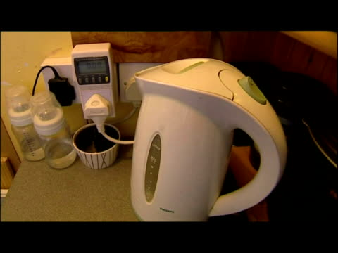 interior shots various examples of energy use in the home . anon woman using washing machine, boiling kettle, lights, light switches, energy saving... - dvd player stock videos & royalty-free footage