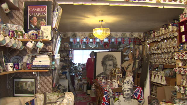 interior shots various items of royal memorabilia on display depicting the queen the queen mother prince charles camilla prince william kate... - souvenir stock videos and b-roll footage