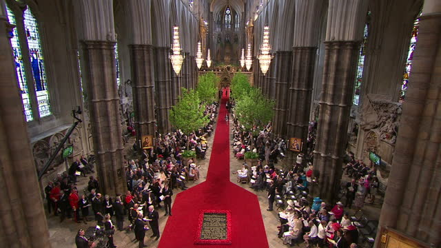 vídeos de stock, filmes e b-roll de interior shots wedding guests sat inside a full westminster abbey interior high shots guests sat amongst the line of trees lining the abbey sky news... - hóspede