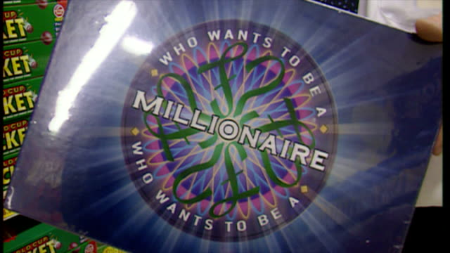 vídeos de stock, filmes e b-roll de interior shots 'who wants to be a millionaire' board game being stacked on shelves in toy shop. on december 18, 1999 in london, england. - game show