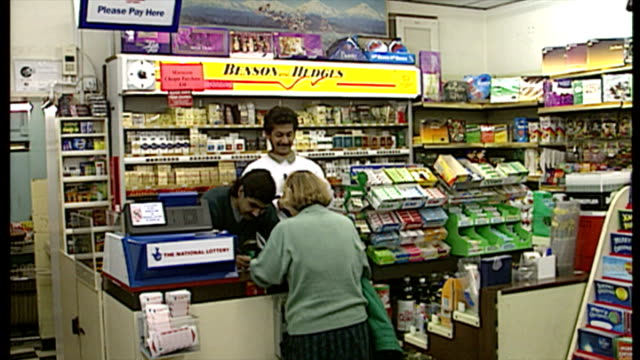 interior shots, woman buys lottery tickets at a corner shop on november 14, 1994 in london, england. - lotterie stock-videos und b-roll-filmmaterial