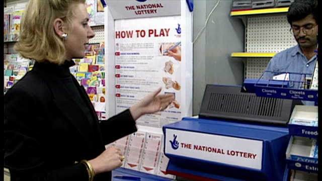 stockvideo's en b-roll-footage met interior shots, woman fills in and buys lottery ticket in newsagent on november 8, 1994 in london, england. - loterijlootje