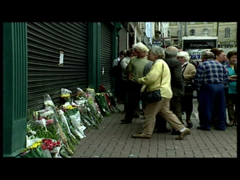 vídeos de stock, filmes e b-roll de interior shots woman reads newspaper headline about omagh bombing by real ira in shop exterior shot newspaper billboards in sixmilecross about... - primeira página de jornal