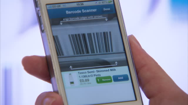 Interior shots woman scans Tesco product bar codes on large electronic display board with her smart phone Tesco Virtual Shopping Shots on August 06...