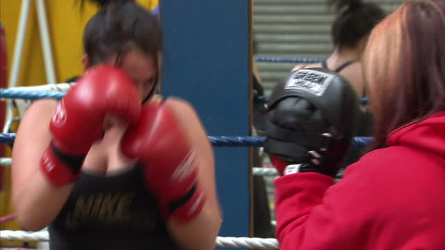 interior shots women spar boxing in gym with trainer women boxers spar in training on august 09, 2012 in london, england - boxing women's stock videos & royalty-free footage
