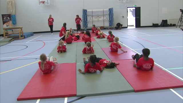 interior shots young primary school children stretching and doing basic gymnastics on gym matts- all wearing beth weddle academy t-shirts, beth... - all shirts stock-videos und b-roll-filmmaterial