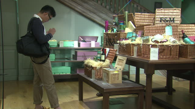 interior showing shoppers looking at famous fortnum and mason hamper baskets hamper baskets on display in london store on june 29 2014 in london... - hamper stock videos and b-roll footage