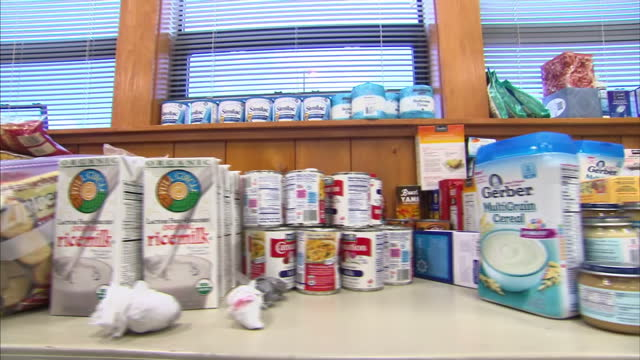 interior shows people queue to receive donated food being given out by volunteers lots of donated food on counter top and people at tables in... - oso washington stock videos & royalty-free footage
