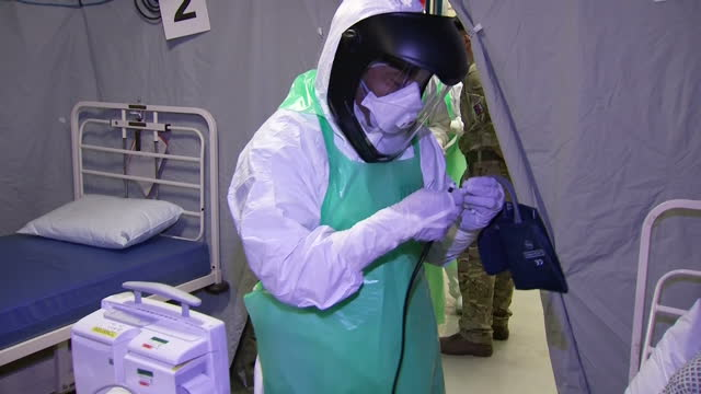 interior shows practice patient in bed and health worker running through drill as if the was an ebola patient in for treatment - practice drill stock videos & royalty-free footage