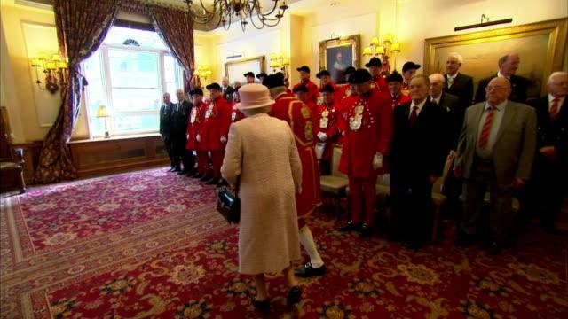 stockvideo's en b-roll-footage met interior shows queen elizabeth enters room for photograph, royal waterman in position, queen elizabeth takes seat on front row, joined by prince... - aan elkaar bevestigd