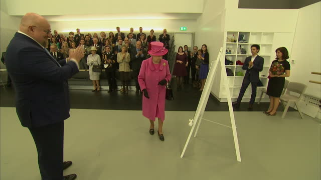interior shows queen elizabeth gets up from seat to unveil plaque on easel to applause on march 20 2014 in london england - staffelei stock-videos und b-roll-filmmaterial