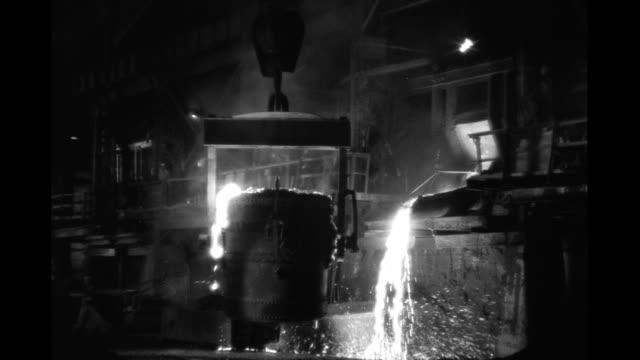 Interior steel mill crane carries large vat of molten steel Interior steel mill on January 01 1930