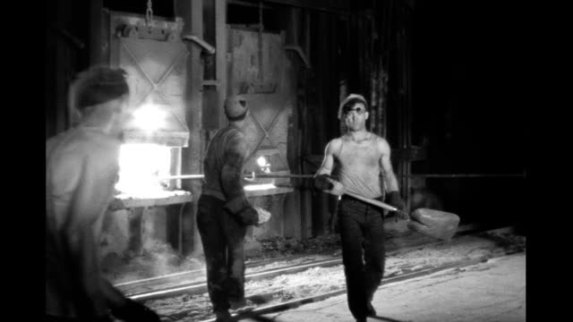 vídeos de stock, filmes e b-roll de interior steel mill men shoveling coal into furnace interior steel mill on january 01 1930 - fornalha