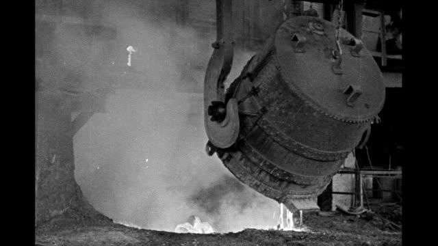 Interior steel mill men tend giant vat of molten steel as it pours Interior steel mill on January 01 1930