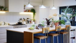Interior view of beautiful kitchen with island counter and house plants in family home - shot in slow motion
