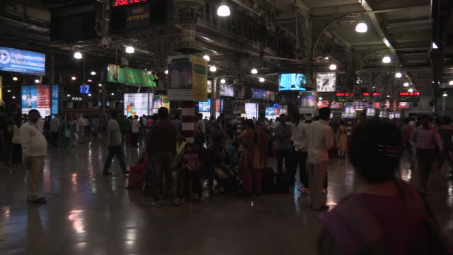 Interior view of people waiting on the Chhatrapati Shivaji Terminus concourse Mumbai Maharashtra India FKAD675A Clip taken from programme rushes...