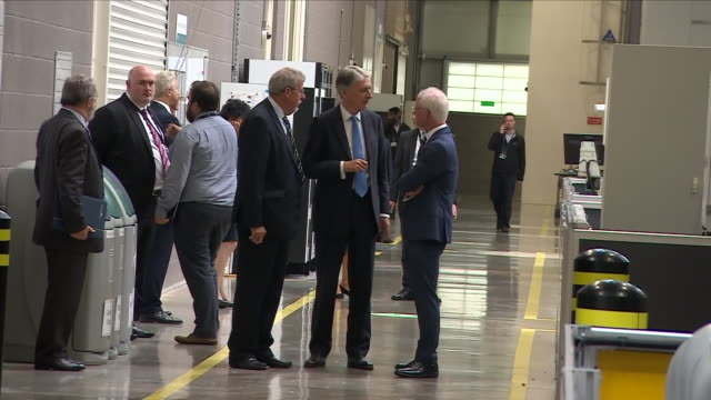interior view of phillip hammond the chancellor as he is deep in conversation with managers as they walk along a corridor at mct manufacturing... - フィリップ ハモンド点の映像素材/bロール