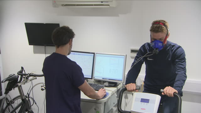 Interior view of Physiologist Jim Pate monitoring the breathing rate of a young athlete riding on a spinner bike on 21st August 2018 at the Centre...