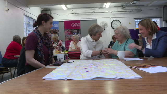 vidéos et rushes de interior view of prime minister theresa may bringing cups of tea into the main hall at vauxhall gardens community centre and sits down and talks with... - centre culturel