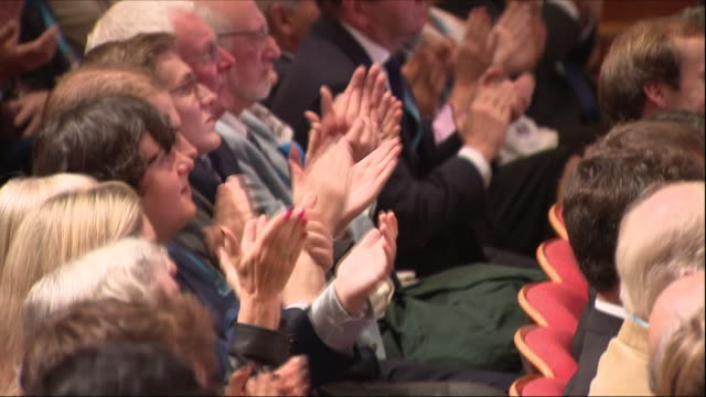 vídeos de stock e filmes b-roll de interior view of the crowd listening and applauding prime minister theresa may on stage delivering her keynote speech at the conservative party... - conferência partidária
