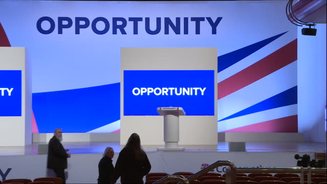 vídeos de stock e filmes b-roll de interior view of the empty main conference hall at the conservative party conference in birmingham being made ready for the prime ministers key note... - conferência partidária