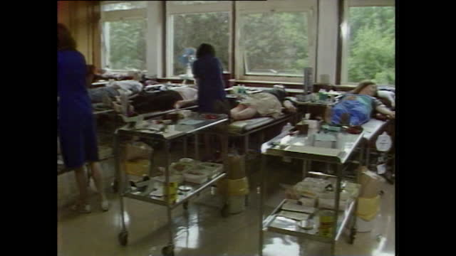 interior views of a blood donor centre in the united kingdom, with donors lying on beds and nurses checking blood pressure; 1983. - wide shot stock videos & royalty-free footage