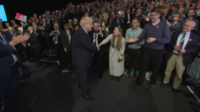interior views of boris johnson walking into the conference centre hall to make his statement speech and being cheered and greeted by members of the... - convention stock videos & royalty-free footage
