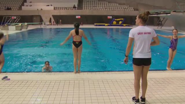 interior views of grace reid teaching young children diving techniques at poolside in front of a tokyo 2020 countdown clock at the london aquatics... - poolside stock videos & royalty-free footage